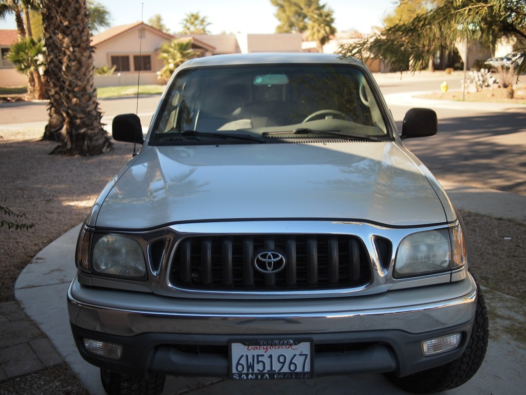 A 2002 Toyota Tacoma, Silver in color. View is from the front grill looking into the drivers seat. Truck is parked.
