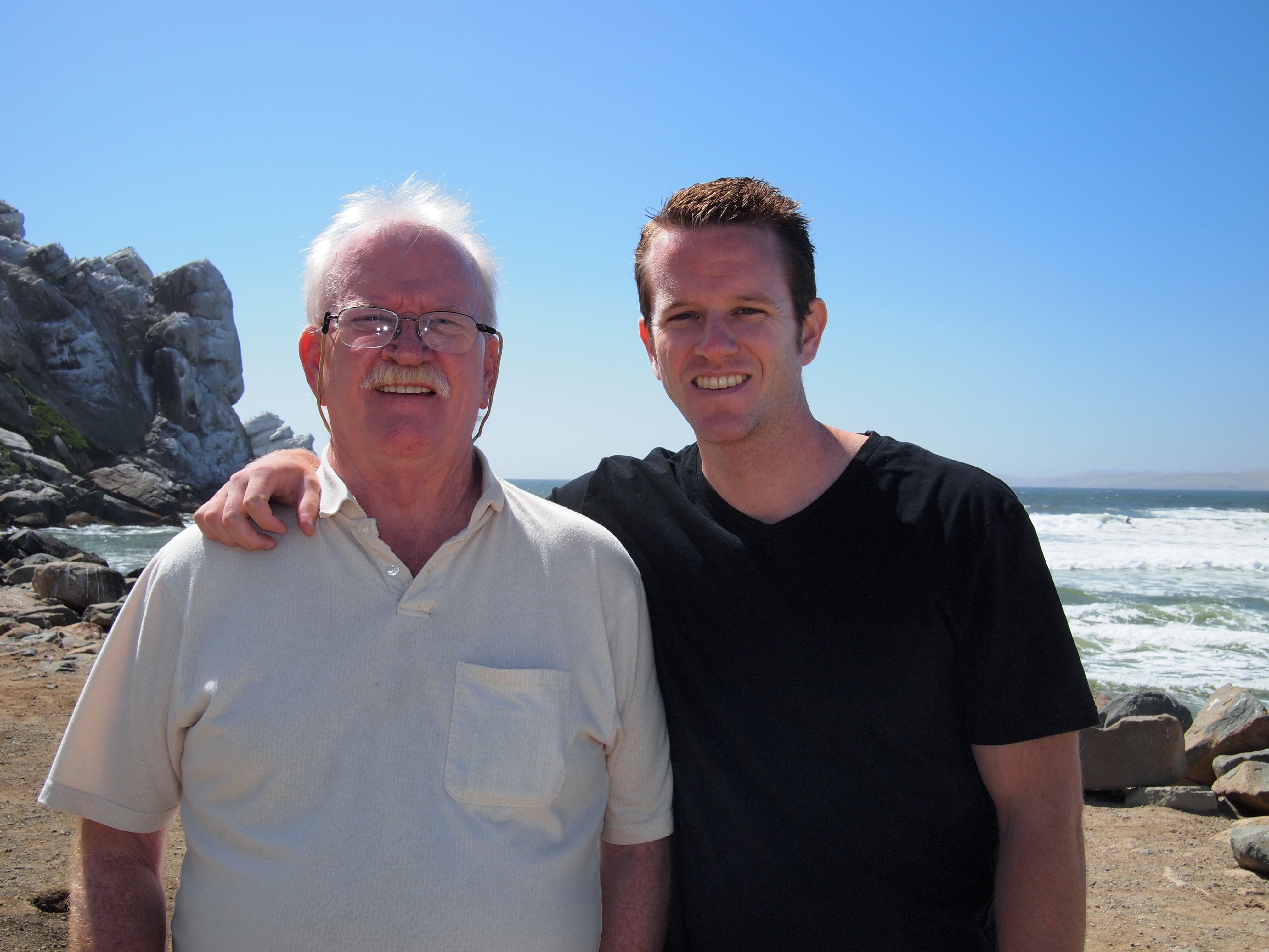 A sunny day with Brandon standing next to his Dad with the beach in the bakground. Brandon' s arm is around his Dad.