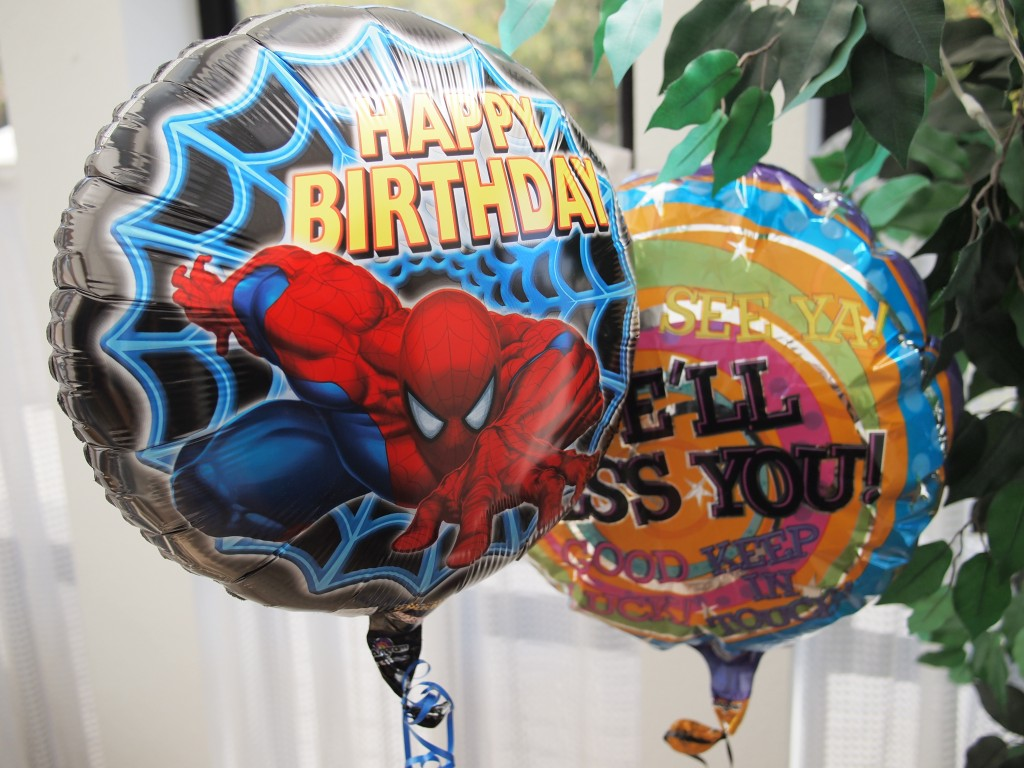 "A spider man birthday balloon next to a ""We'll miss you"" balloon"