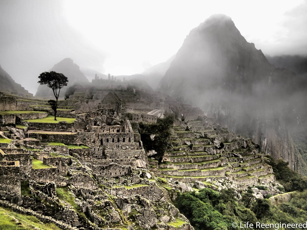 Dramatic photo of the ruins at Machu Picchu with Waynapicchu mountain shrouded in fog in the background