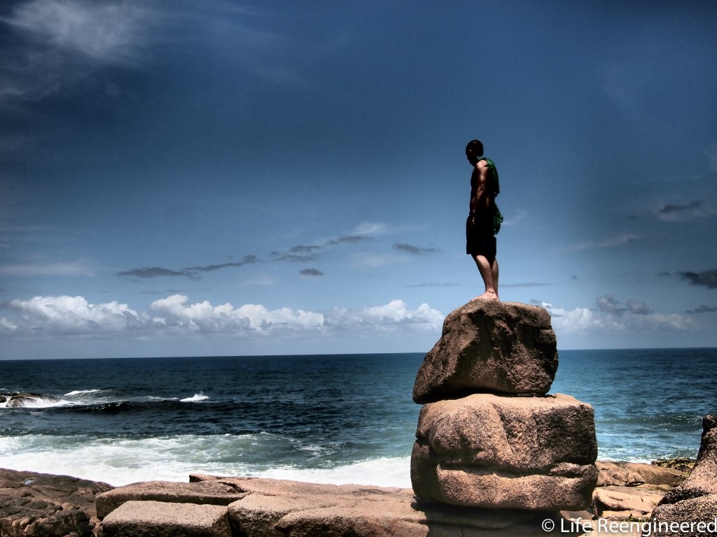 Brandon at the Beach, standing on a stack of square rocks, looking out over the sea, with a Brazilian flag draped over his shoulders.