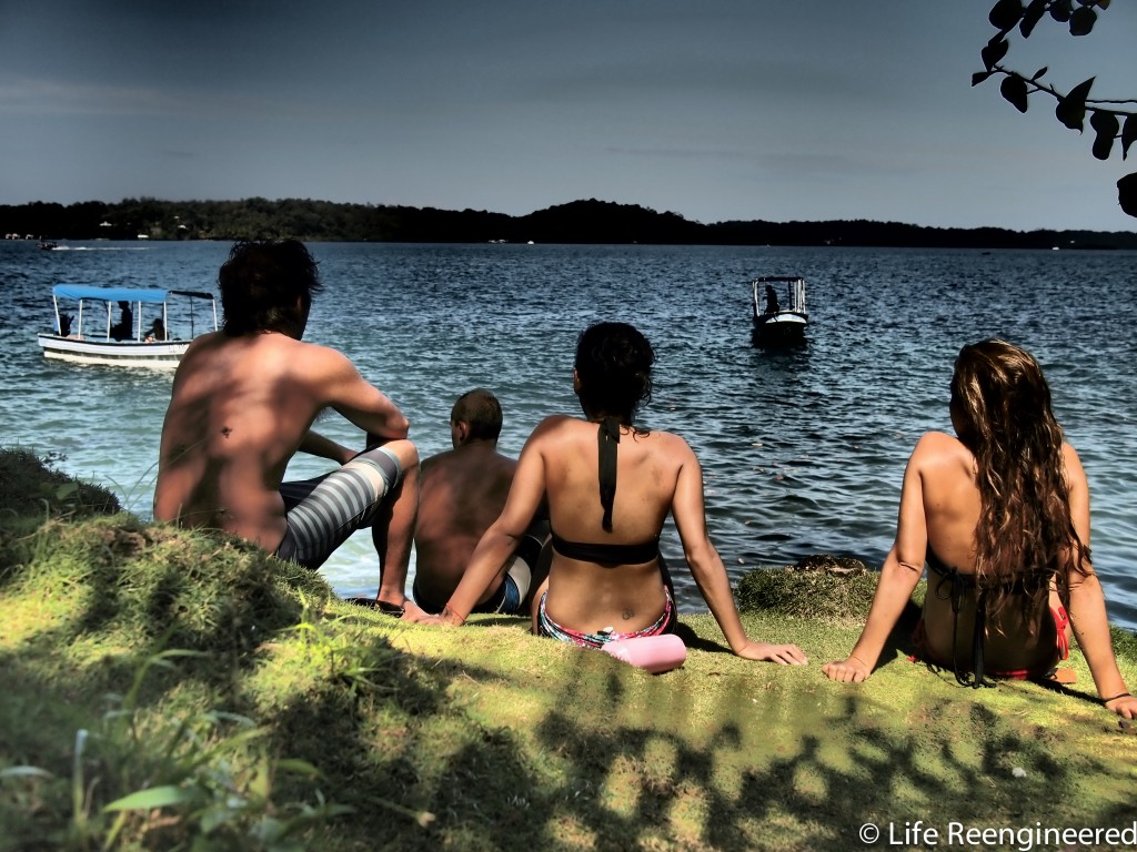 Four friends facing away from the camera, sitting staring at the ocean from a grassy knoll in Bocas Del Toro, Panama.