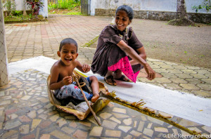 A smiling child, sitting on a banana leaf, with his mother laughing in the background.