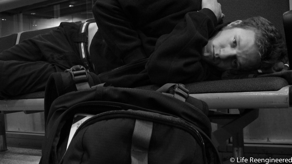 Brandon laying across some chairs in an airport in London, about to go to sleep.