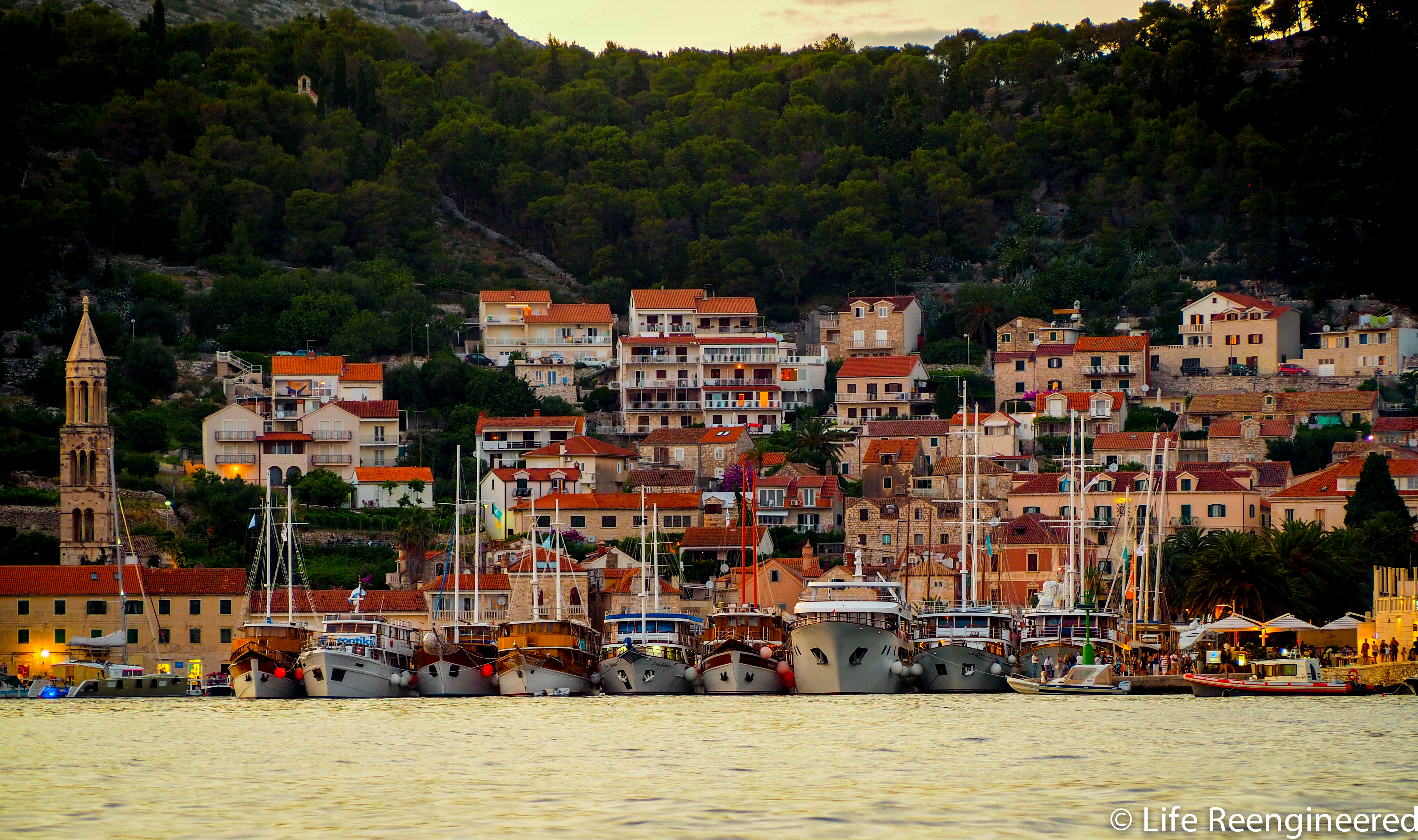 Old Town Hvar in the dying light. Cruise ships are tied together in front of the old town